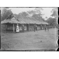 [Africains et missionnaire devant une case]