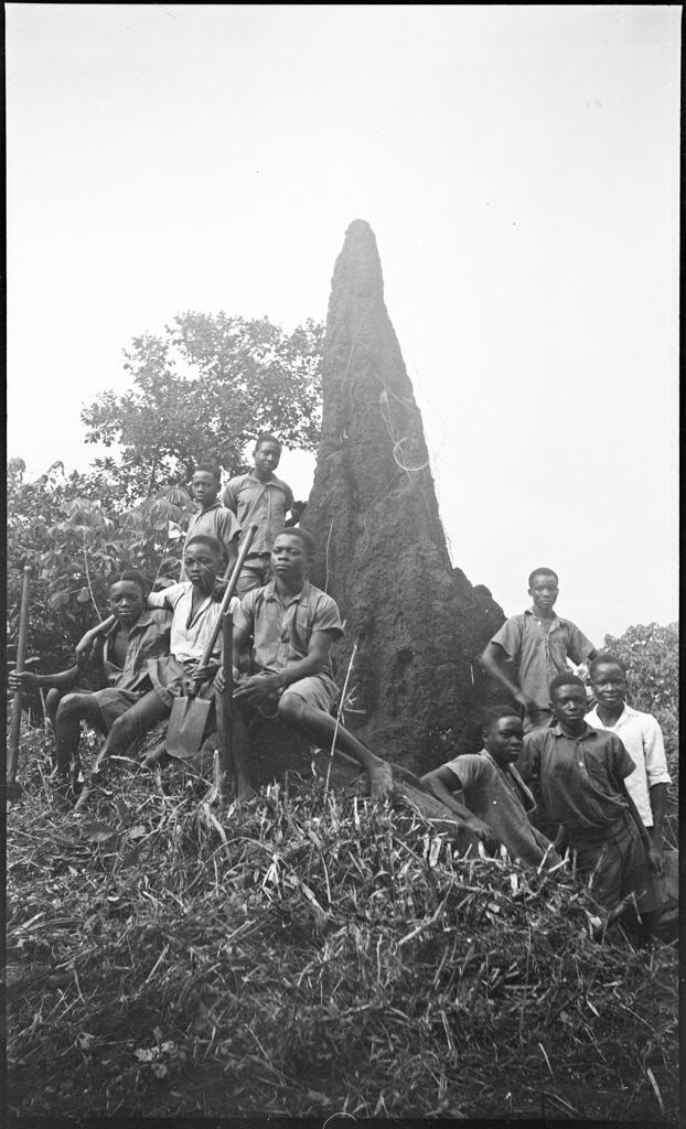 [Africains posant devant une termitière]