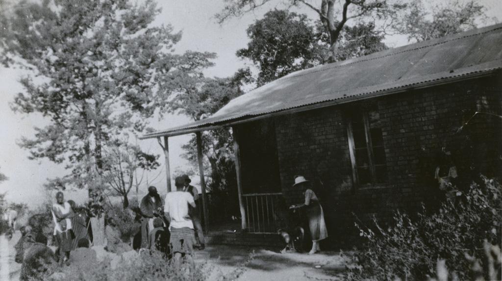 Au dispensaire de Mabumbu, Melle Perrier et des Africains devant le bâtiment