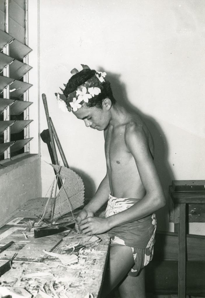 Centre éducatif de Moria. Un garçon fabrique une maquette de pirogue à balancier