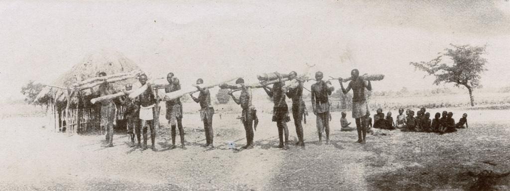 Chez Mokutulu, hommes portant des troncs sur leurs épaules