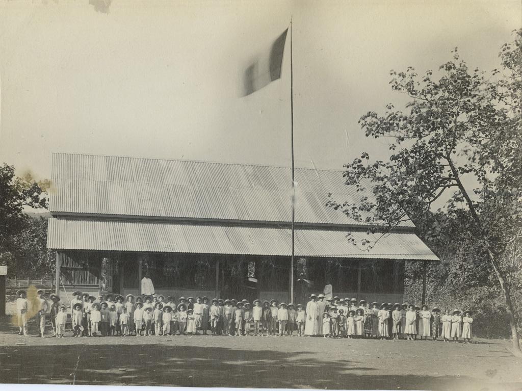 Ecole de Papeete, maîtres et jeunes élèves groupés devant leur école, un drapeau français a été hissé