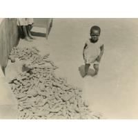 Enfant de la pouponnière devant un tas de manioc et patates