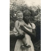 Enfant de missionnaire dans les bras d'une jeune fille indigène