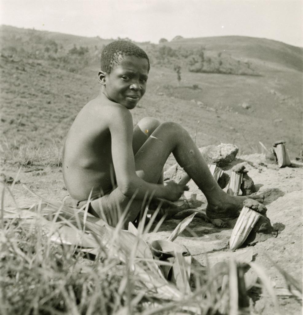 Enfant du Grassfield faisant sortir des termites - qu'il mangera