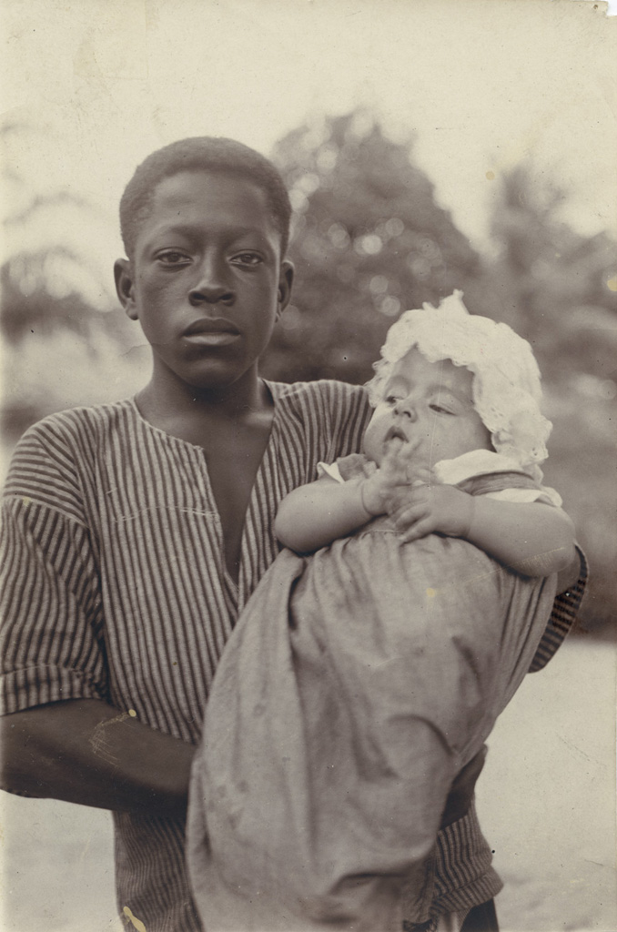 [Enfant noir avec un bébé blanc dans les bras]