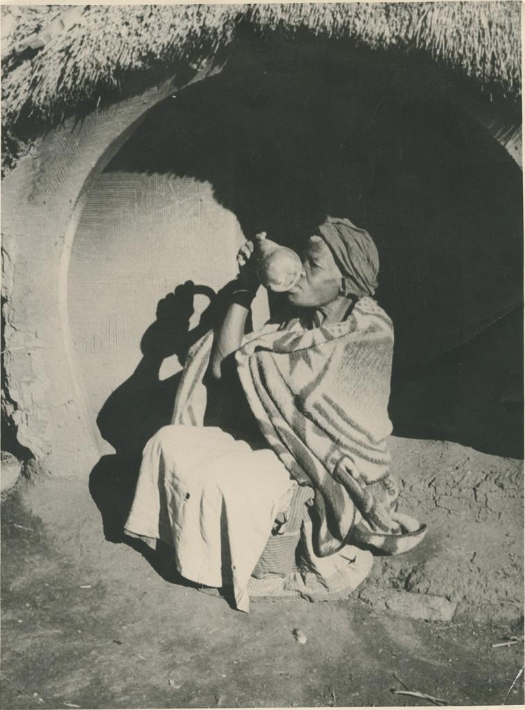 Femme buvant de la bière dans une calebasse à l'entrée de sa hutte