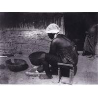 Femme écrasant du maïs entre deux pierres