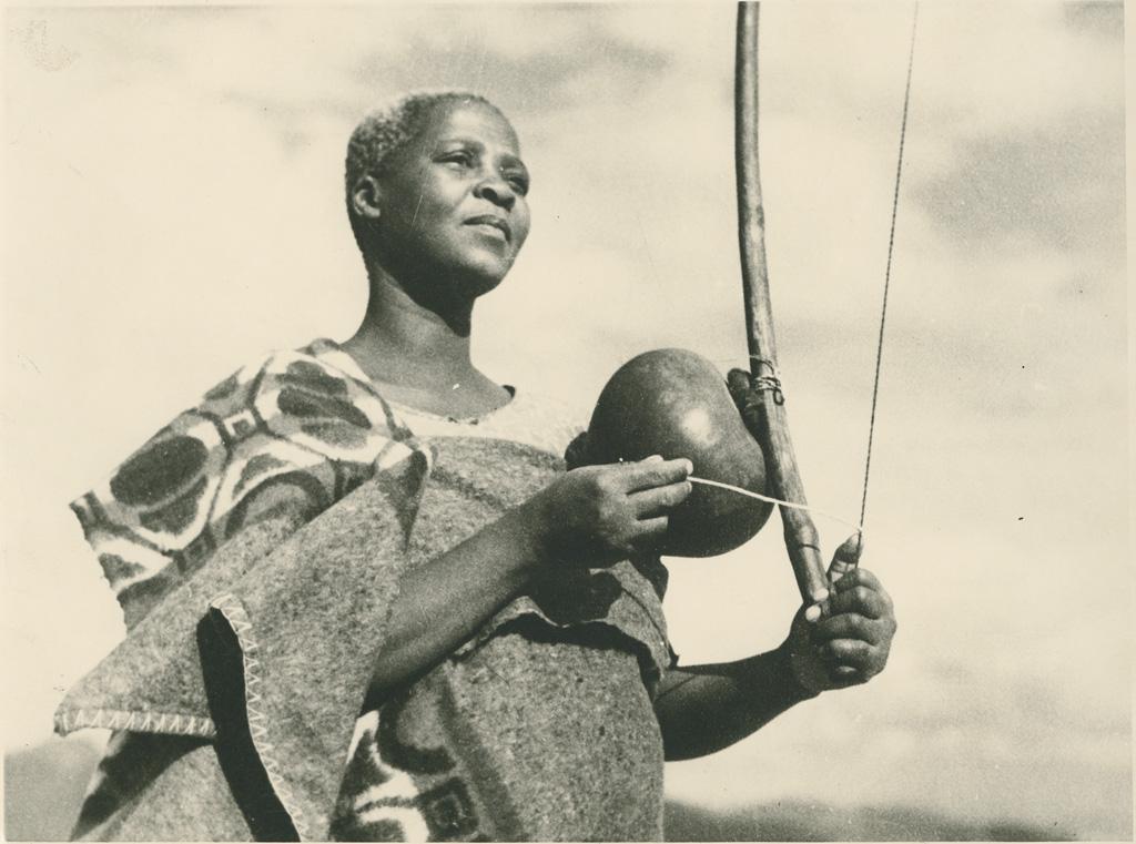 """Femme jouant d'un instrument appelé """"Thomo"""" ; il se compose d'un arc, d'une corde et d'une calebasse"""