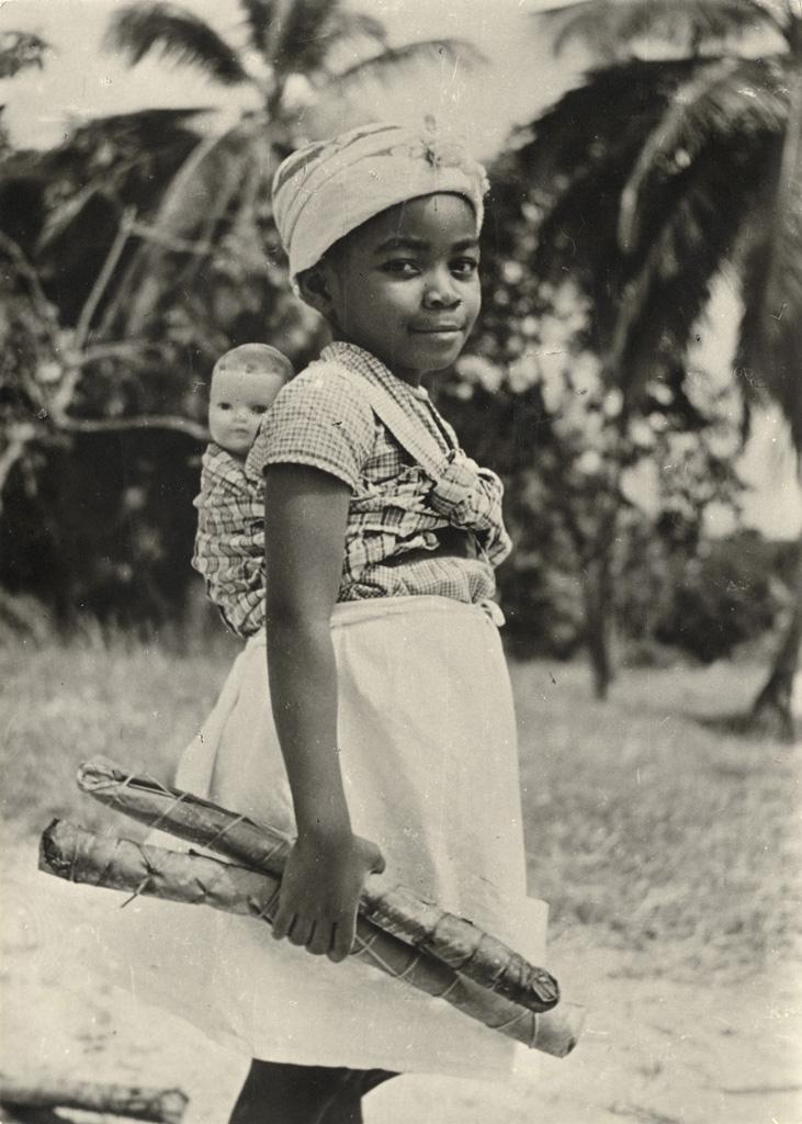 Fille du moniteur Obame, avec poupée sur le dos et batons de manioc à la main