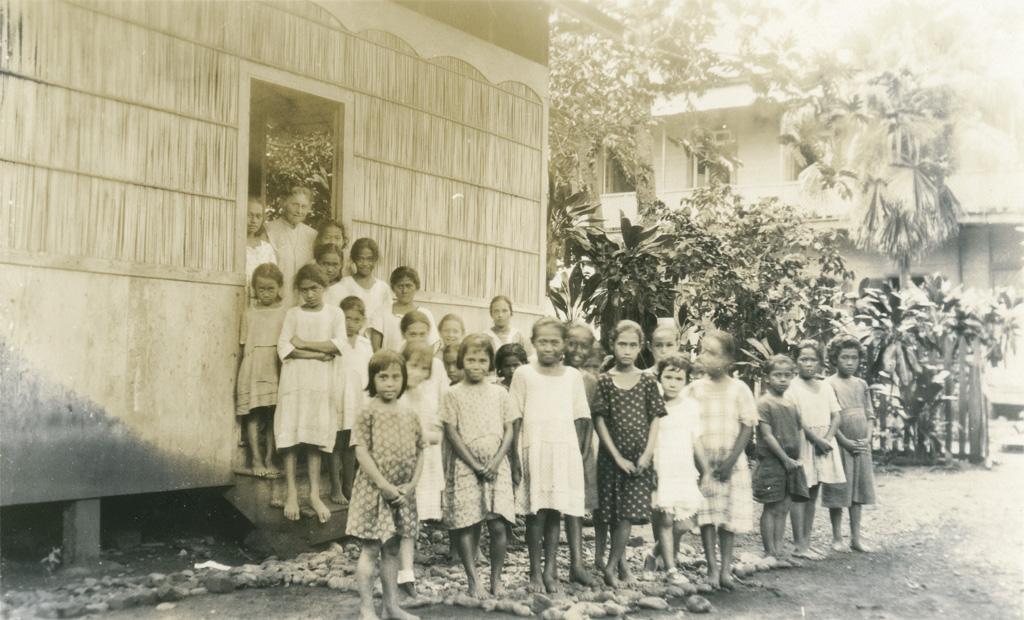 Fillettes sortant d'une case en bambou qui sert de bibliothèque et de salle, pour les cours de religion et autre, Papeete