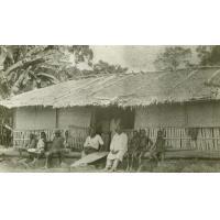 Gabonais assis devant une case