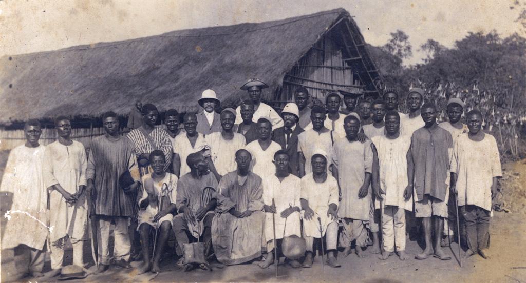 Groupe d'homme entourant deux missionnaires