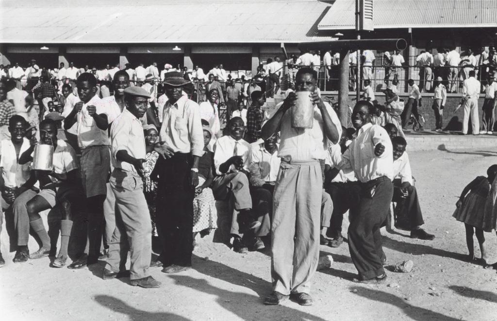 Hommes et femmes dans la cour d'une usine