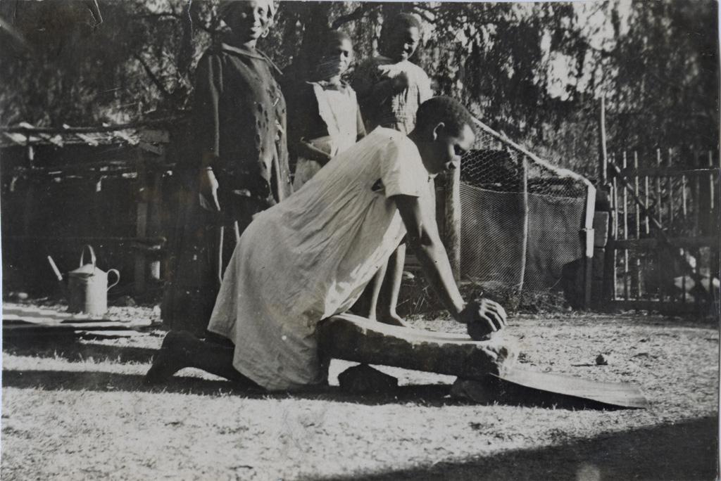 Jeune fille moulant du grain sur une pierre plate
