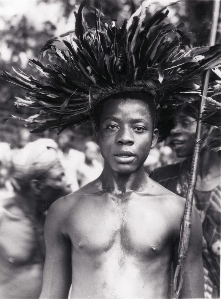 Jeune homme avec lance et coiffe de plumes
