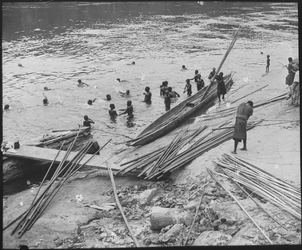 [Jeunes hommes dans l'eau chargeant du bois sur une embarcation]