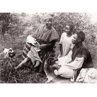 Nji Fewu montrant des motifs de broderie à deux jeunes gens