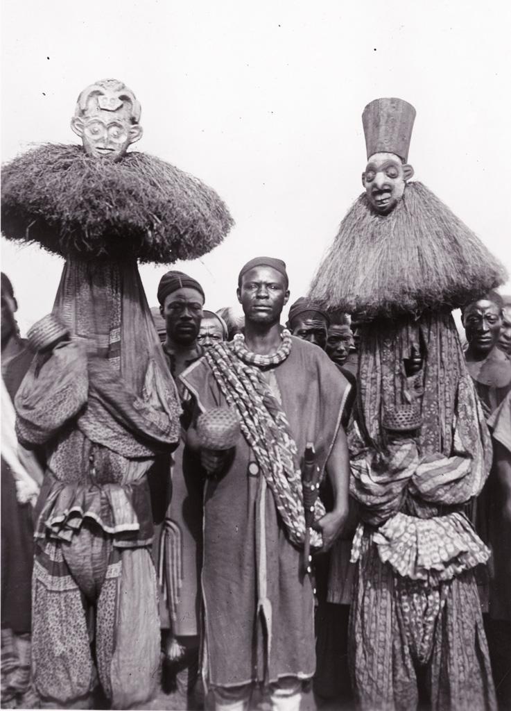 Nji Wamben entouré de deux hommes masqués et costumés
