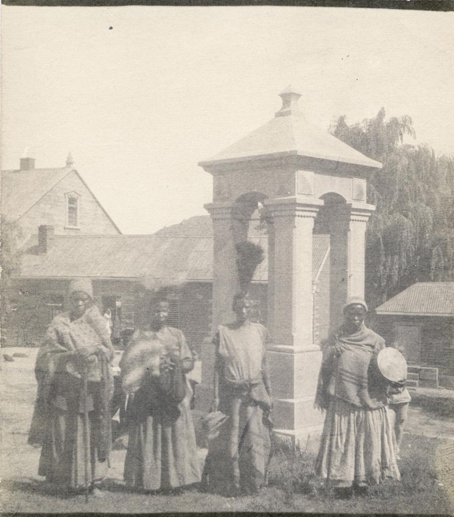 Quelques femmes en costume de danse devant le clocher