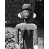 Statue en bois couverte de perles (orangé vif et blanc, seins noirs), à Bameka