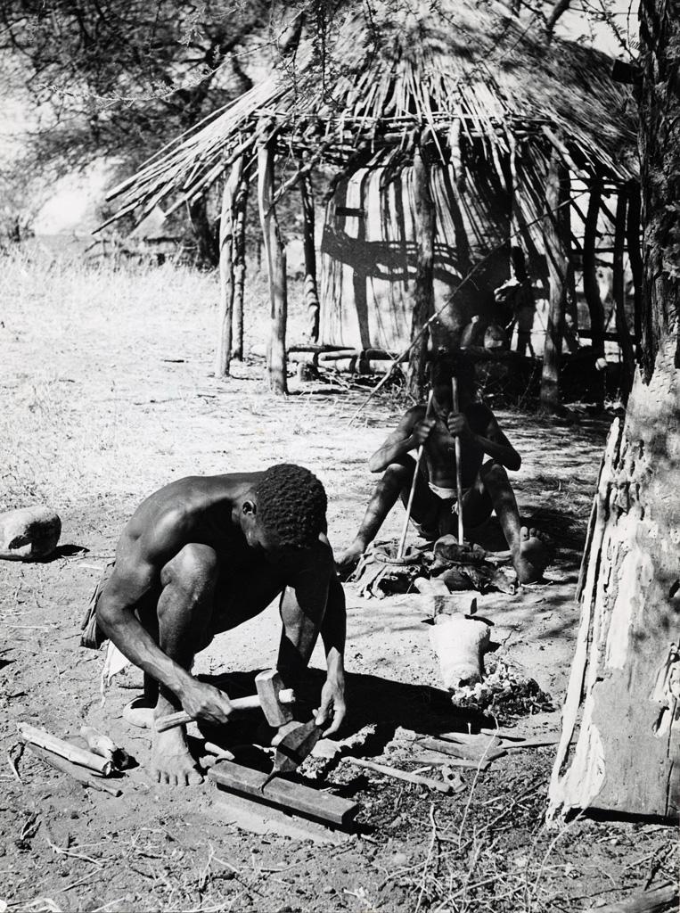 Tandis que son jeune assistant manoeuvre vigoureusement un soufflet en peau de chèvre pour maintenir l'ardeur du feu, un forgeron Batenga travaille un fer de lance