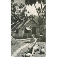 Tetua râpe le coco, devant sa case