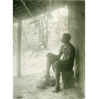 Un malade mettant la plaie de son pied au-dessus d'un feu dans lequel il fait brûler de la médecine indigène