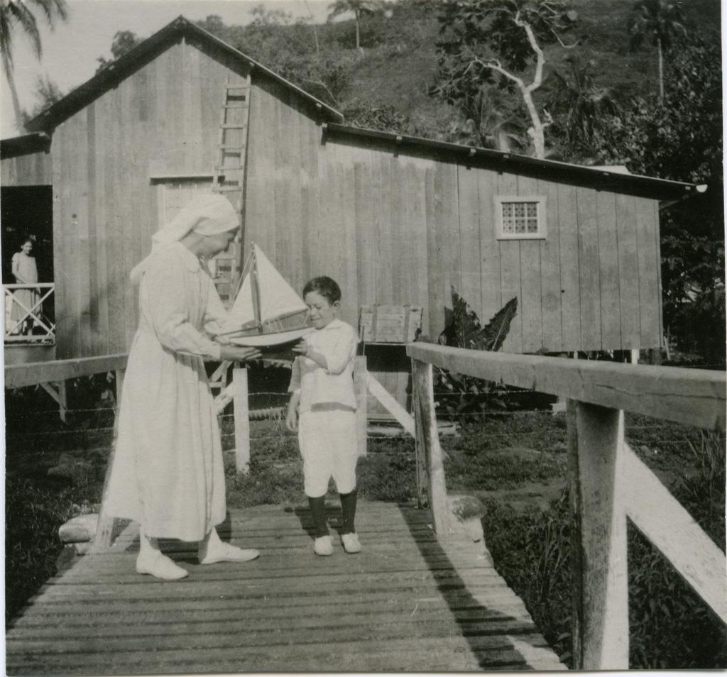 Une diaconesse en compagnie d'un petit garçon, nommé Tamu, sur un pont menant à la léproserie d'Orofara