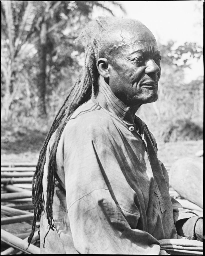 Vieux sculpteur, ses longs cheveux révèlent sa qualité de féticheur
